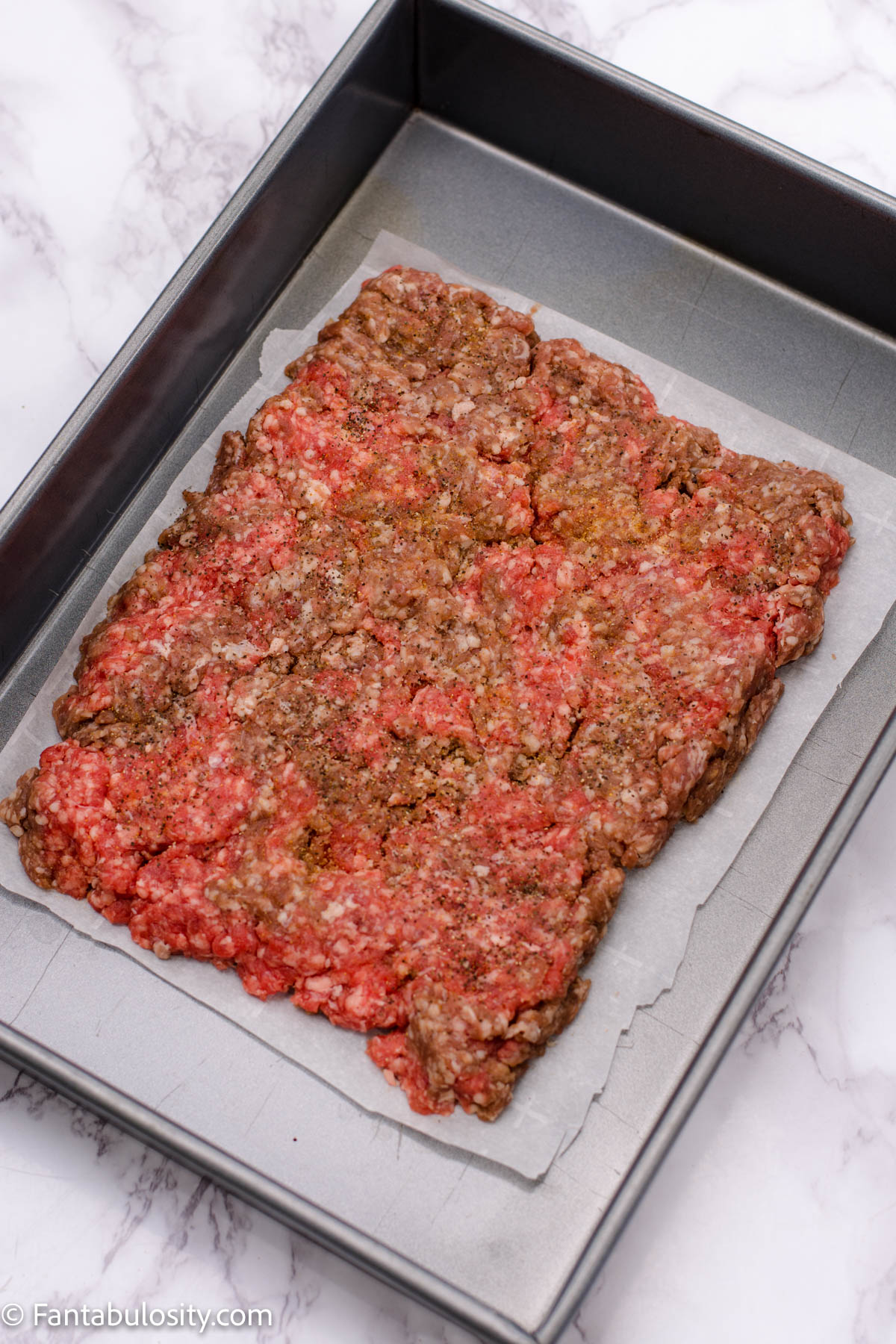 Raw ground beef in baking pan with sides