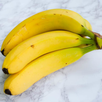 Bananas in bundle on white counter