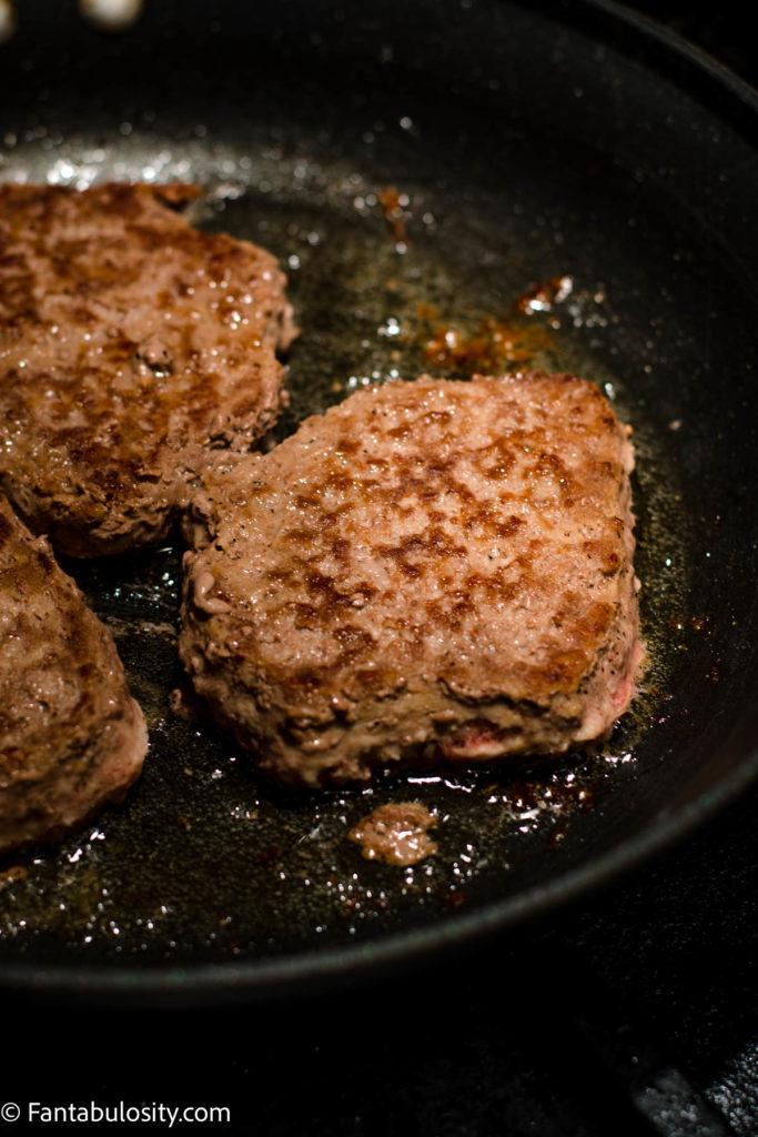 Flip burger over in pan