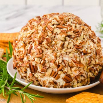 cheese ball on white plate with pecans