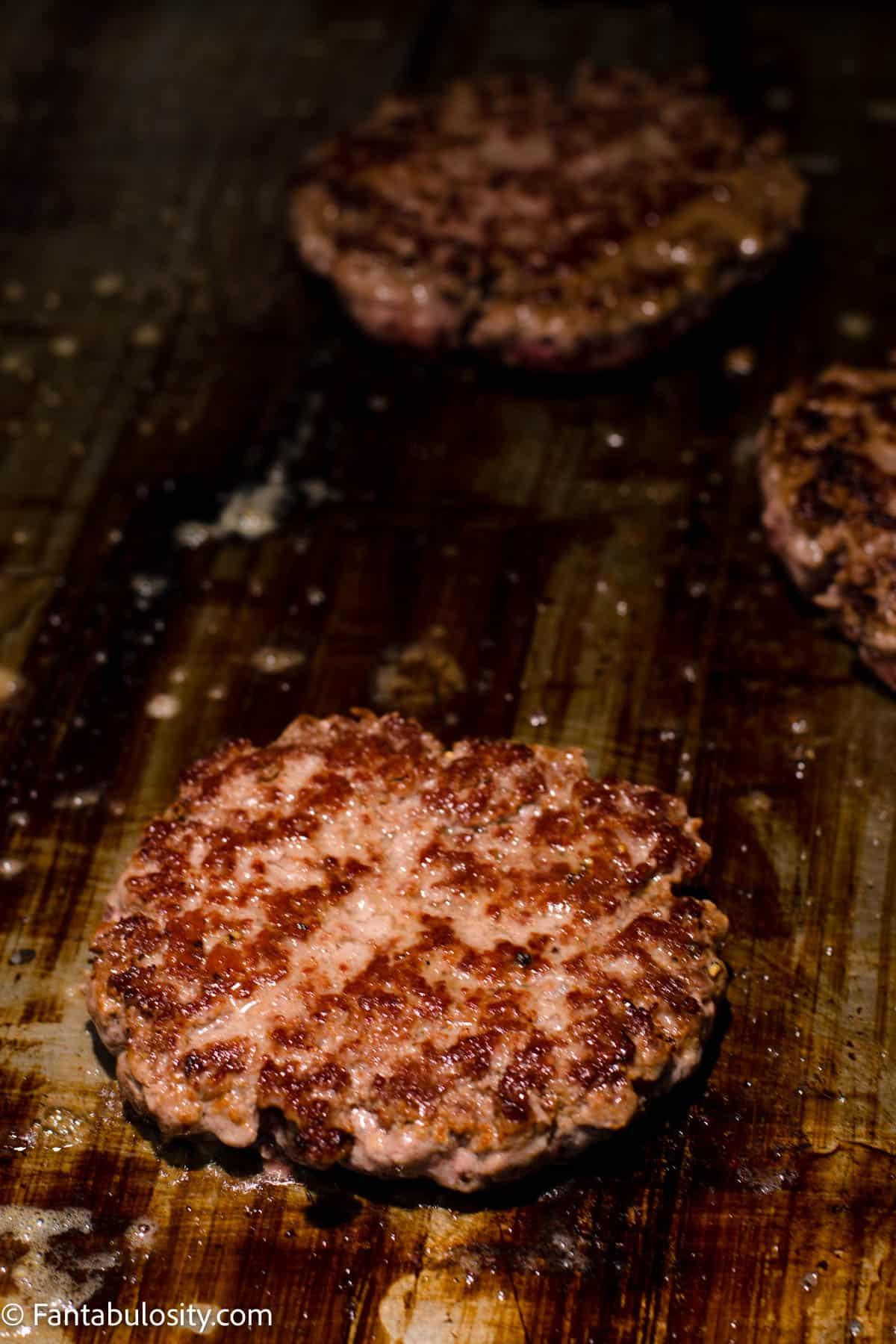 Flipped burger patties cooking